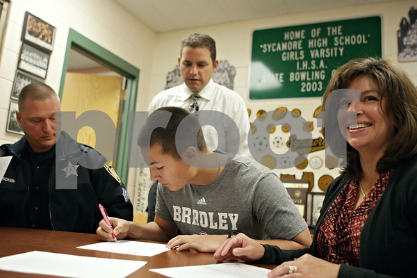 Rob Winner – rwinner@shawmedia.com<br /> <br /> Nathan Haacker (center) signs a letter of intent to play baseball at Bradley University while being accompanied by his father Jim Haacker (left) and mother Heather Haacker (right) and Sycamore baseball coach Jason Cavanaugh (back) during a signing event at Sycamore High School on Wednesday, Nov. 13, 2013.