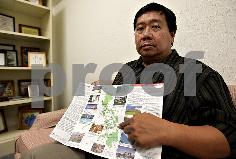 Monica Maschak - mmaschak@shawmedia.com<br /> Training Coordinator Rey Ty, with Northern Illinois University's International Training Office, holds a map of the Philippines, where he has relatives he is unable to contact amid the aftermath of super typhoon Haiyan.
