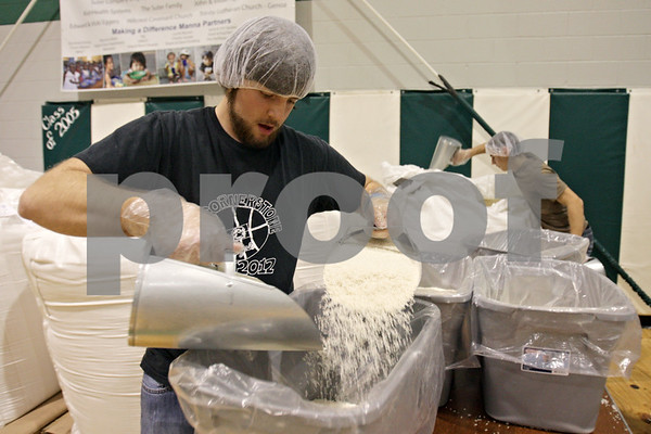 Rob Winner – rwinner@shawmedia.com<br /> <br /> Andrew Stahl (left) of Sycamore and Darshon Kelly Johnson of Genoa fill tubs with rice during the Feed My Starving Children mobile pack event at Cornerstone Christian Academy in Sycamore, Ill., Thursday, Nov. 14, 2013. The meals packed by the volunteers during this four-day event will be shipped across the world to fulfill the nutritional needs of starving children.