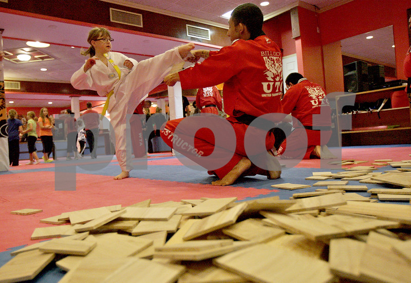 Monica Maschak - mmaschak@shawmedia.com<br /> Felicia Kapity, 7, a yellow belt, breaks a board at Billy Cho's United Tae Kwon Do Center for a Break-a-thon to benefit eight-year-old Tyler Neppl on Friday, November 15, 2013. Neppl has a rare genetic disorder called neurofibromatosis. Hundreds of Neppl's classmates, neighbors and friends came out to break boards at the Tae Kwon Do center where he is an orange belt.