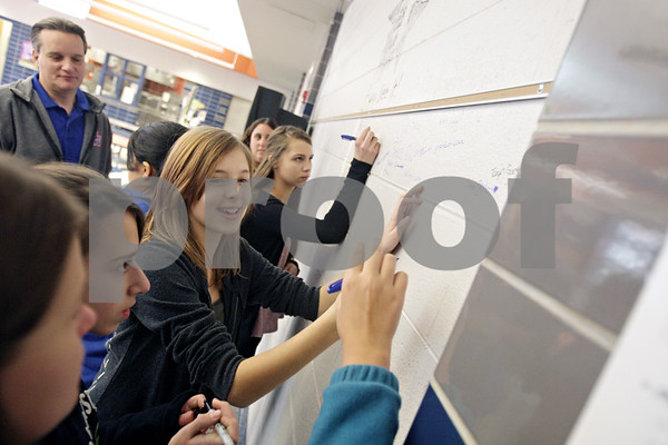 """Rob Winner – rwinner@shawmedia.com<br /> <br /> Eighth grader Jayna Masters signs a wall at Genoa-Kingston Middle School to show her commitment to stopping and reporting bullying on Friday, Nov. 22, 2013. The """"I want you Say it if you See it!"""" wall is part of a monthlong event to encourage students to stop being bystanders when they see bullying."""
