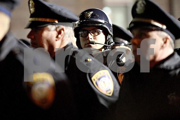 Monica Maschak - mmaschak@shawmedia.com<br /> DeKalb Patrolman Lance Reinbolz stands among other DeKalb officers for the raising of the American Flag in front of the new DeKalb Police Station on Friday, November 22, 2013.