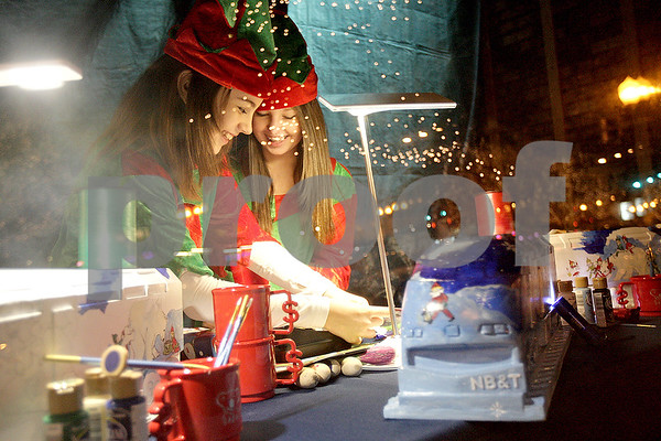 Monica Maschak - mmaschak@shawmedia.com<br /> Nicole Cox and Faith O'Higgins, for NB&T Bank, wrap presents while dressed as elves during Moonlight Madness in downtown Sycamore on Friday, November 22, 2013. Storefronts were filled with holiday scenes.