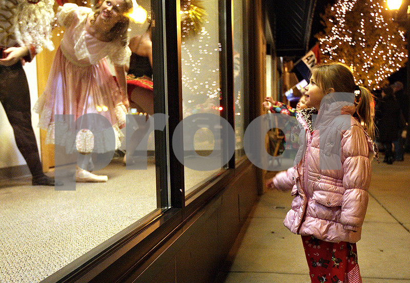 Monica Maschak - mmaschak@shawmedia.com<br /> Kylan Hill, 4, watches a group from Beth Fowler School of Dance perform a scene from The Nutcracker in a window of the city building during Moonlight Madness in downtown Sycamore on Friday, November 22, 2013. Storefronts were filled with holiday scenes.