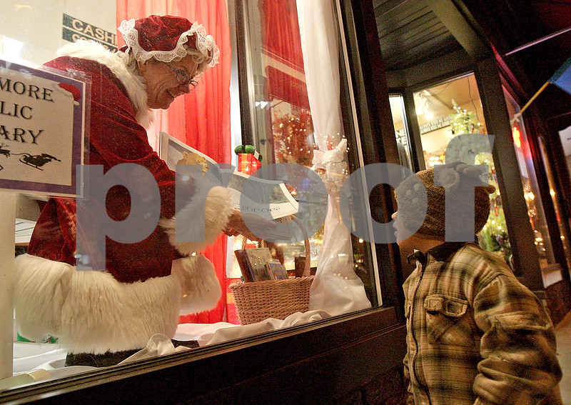 Monica Maschak - mmaschak@shawmedia.com<br /> Sarah Tobias, from the Sycamore Public Library, as Mrs. Claus, reads a book to Jackson Lind, 2, through the window of Sweet Earth Jewelry during Moonlight Madness in downtown Sycamore on Friday, November 22, 2013. Storefronts were filled with holiday scenes.