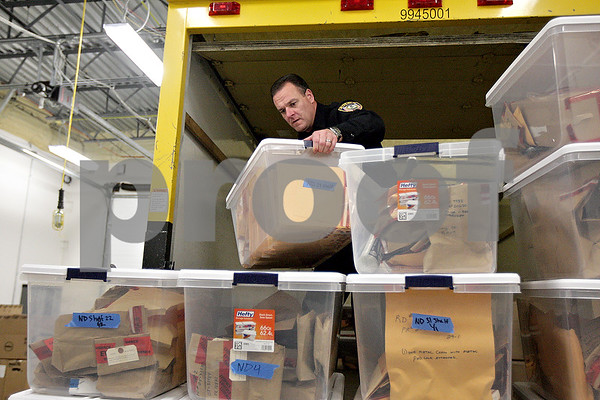Monica Maschak - mmaschak@shawmedia.com<br /> Patrol Officer Jeff Winters unloads bins of evidence from a truck at the new DeKalb Police Station on Thursday, November 21, 2013. Police personnel have been gradually packing up the old police station in the DeKalb Municipal Building for the move. The new police station is said to be functional beginning Friday at 7:00 a.m.
