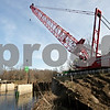 Rob Winner – rwinner@shawmedia.com<br /> <br /> A crane is used to place steel sheeting for a cofferdam in the Kishwaukee River as construction for the Five Points Road bridge continues in Kingston, Ill., Friday, Nov. 15, 2013.