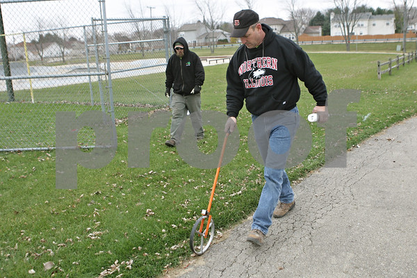 Rob Winner – rwinner@shawmedia.com<br /> <br /> Todd Bex (front) and Josh Clark of the DeKalb Park District begin taking measurements and making a layout for the temporary dog park located at Katz Park in DeKalb, Ill., Wednesday, Nov. 20, 2013.