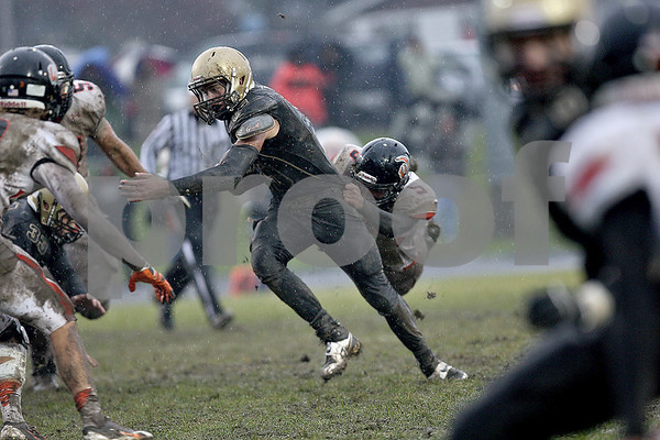 Monica Maschak - mmaschak@shawmedia.com<br /> Quarterback Devin Mottet pulls a defenseman through the mud in the fourth quarter of a Class 5A Quarterfinal game against Lincoln-Way West on Saturday, November 16, 2013. The Spartans beat the Warriors 21-14 and will move on to play Montini next week.