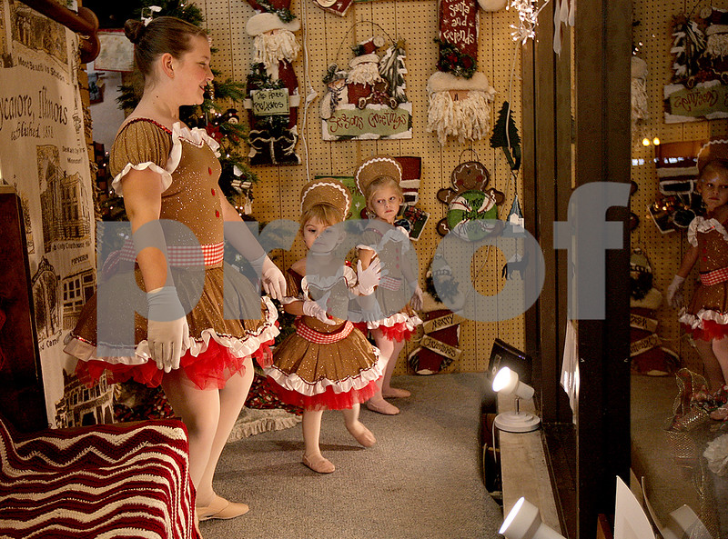 Monica Maschak - mmaschak@shawmedia.com<br /> Kaitlyn Costello, 12, Leah McGrath, 3, and Ava Haptonstall, 3, as gingerbread girls from the Sycamore Performing Arts Academy, dance in the window of Made Just For You Gifts during Moonlight Madness in downtown Sycamore on Friday, November 22, 2013. Storefronts were filled with holiday scenes.