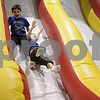 Rob Winner – rwinner@shawmedia.com<br /> <br /> Kaden Ladas (left), 9, and Asher Larson, 6, both of Sycamore go down an inflatable slide inside the Cornerstone Christian Academy gymnasium on Friday afternoon in Sycamore. The Jumpin' Out Friday event includes five bounce houses and obstacle courses. The event is normally held every third Friday of the month, but a special Black Friday event was added this year.