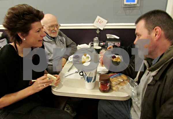 Andrea Azzo – aazzo@shawmedia.com<br /> <br /> Volunteer Bea Corbin (left to right) takes down orders for Sycamore resident John Warford and DeKalb resident Patrick Behm on Thanksgiving night at Feed'em Soup in DeKalb.