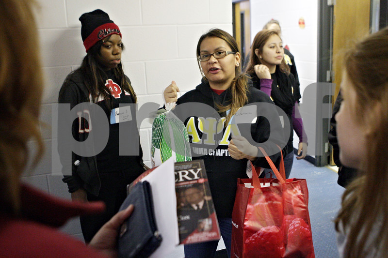 Rob Winner – rwinner@shawmedia.com<br /> <br /> Volunteer Adriana Flores offers to help a client to her car as food baskets for the Thanksgiving holiday were distributed at the Salvation Army in DeKalb on Tuesday, Nov. 26, 2013.