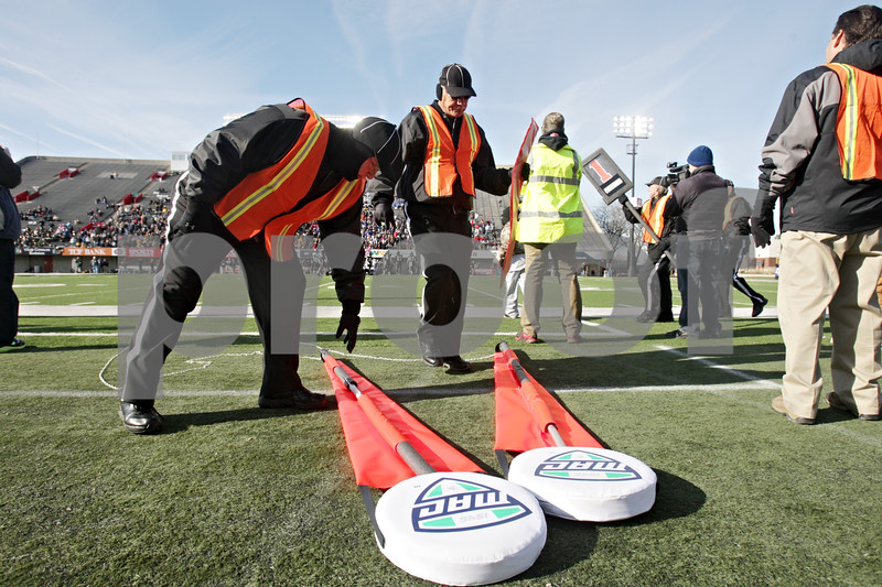 Rob Winner – rwinner@shawmedia.com<br /> <br /> Volunteers Dan Schuster (left) and George Grassmuck of the chain crew reach for the sticks after a break during the Class 1A championship game in DeKalb, Ill., Friday, Nov. 29, 2013.