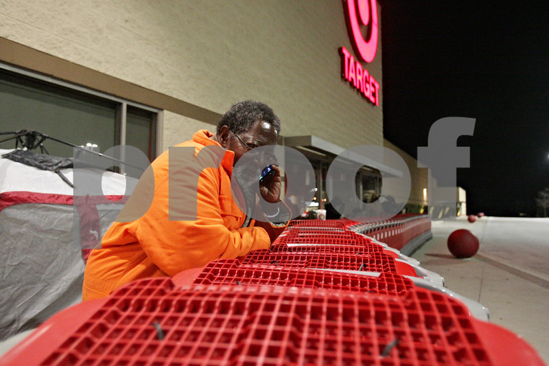 Rob Winner – rwinner@shawmedia.com<br /> <br /> DeKalb resident Art Davis makes a phone call while waiting outside Target in DeKalb on Thursday evening. Davis was relieving his wife, Nancy Richardson, who was the first shopper in line when she arrived at the business at 9 a.m. on Thursday morning. The family planned on purchasing a new television.