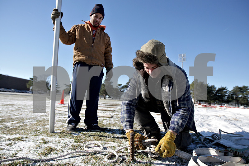 Monica Maschak - mmaschak@shawmedia.com<br /> William Padilla (left) watches as Erich Albrecht, both with Berg Industries, ties rope to stakes as they set up the spirit tents during preparations for the IHSA Football Championships at Huskie Stadium on Wednesday, November 27, 2013.