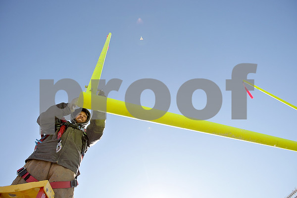 Monica Maschak - mmaschak@shawmedia.com<br /> Pipe fitter Alex Ellsworth, with Northern Illinois University Plumbing Shop, tightens up the last few bolts on the high school goal posts at Huskie Stadium on Wednesday, November 27, 2013. High school regulation goal posts are wider than those used in college.