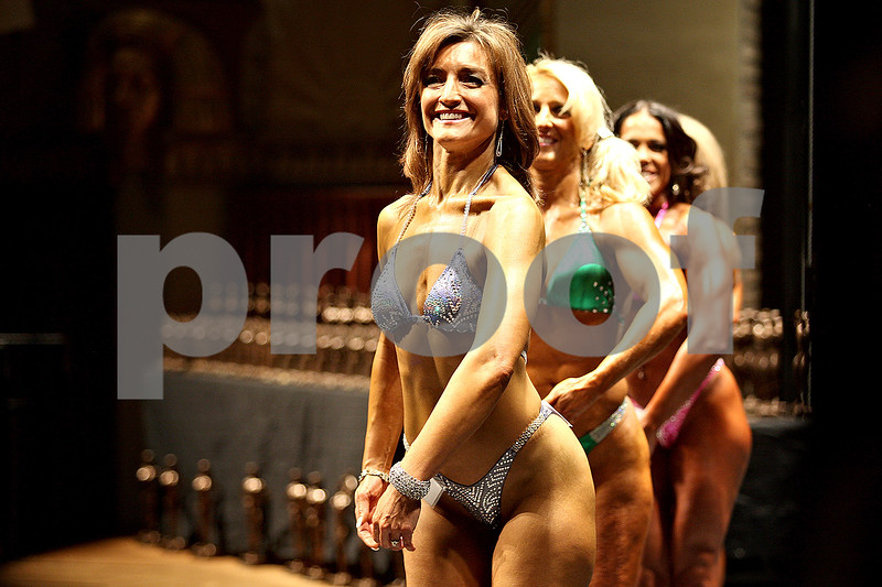 Monica Maschak - mmaschak@shawmedia.com<br /> Female competitors flex to their left for the judges during a bodybuilding competition at the Egyptian Theatre in DeKalb on Saturday, November 23, 2013.