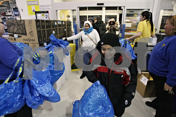 Rob Winner – rwinner@shawmedia.com<br /> <br /> Kevin Ortiz (front), 11, of DeKalb is the first one inside Best Buy which opened at 6 p.m. on Thanksgiving night in DeKalb. Ortiz's aunt, Cristina Campos (left), got in line at 11 p.m. on Wednesday.