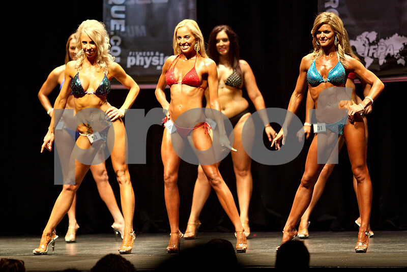 Monica Maschak - mmaschak@shawmedia.com<br /> The women competitors flex on stage for the judges during a bodybuilding competition at the Egyptian Theatre in DeKalb on Saturday, November 23, 2013.