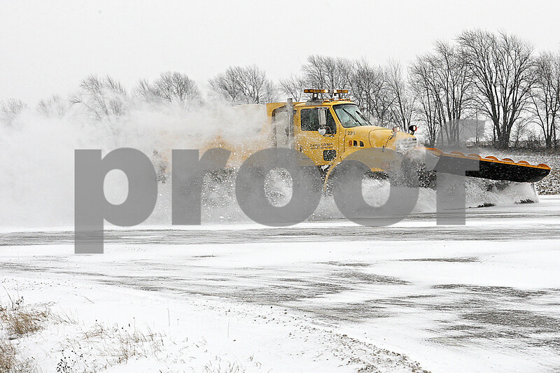 Rob Winner – rwinner@shawmedia.com<br /> <br /> A snow plow is seen traveling south on Peace Road near County Farm Road in DeKalb on Monday afternoon.