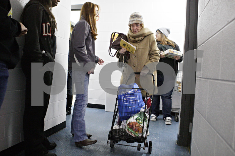 Rob Winner – rwinner@shawmedia.com<br /> <br /> Volunteer Rebekah Lewis (left), 15, helps Anne Rock of DeKalb as food baskets were distributed for the Thanksgiving holiday at the Salvation Army in DeKalb on Tuesday, Nov. 26, 2013. Lewis and her family have helped with the distribution for the last three years.
