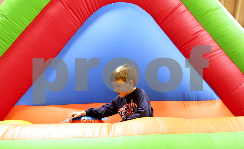 Monica Maschak - mmaschak@shawmedia.com<br /> Nathan Knight, 6, runs through an inflatable obstacle course during Healthy Kids Day at the Kishwaukee YMCA on Saturday, April 27, 2013. The event was for kids in the county to get up and get moving as part of a national YMCA movement to promote healthier lifestyles for children. The event featured educational and physical activities such as games for families, bounce houses and a bike rodeo.