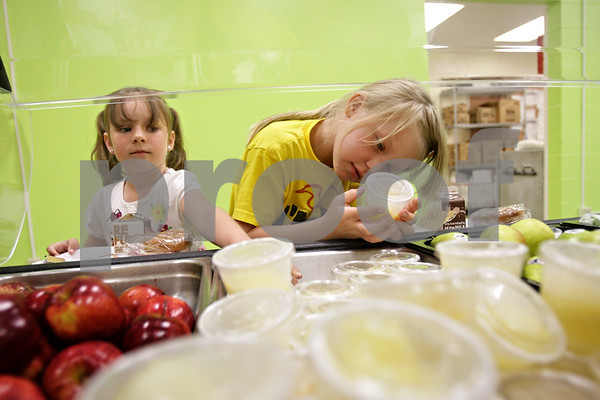 Rob Winner – rwinner@shawmedia.com<br /> <br /> Zoe Elder (left), 5, and Caileen Szostak, 6, each choose a fruit from the healthy food bar at Tyler Elementary School in DeKalb, Ill., Wednesday, May 22, 2013.
