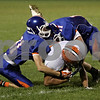Rob Winner – rwinner@shawmedia.com<br /> <br /> Genoa-Kingston defenders Keegan Cline (left) and Tyeler L'Huillier (right) converge for a tackle of Winnebago tight end Isaiah Yanni during the first quarter in Genoa, Ill., Friday, Oct. 4, 2013.