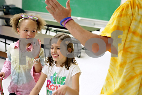 Rob Winner – rwinner@shawmedia.com<br /> <br /> (From left to right) Madison Jacob, 8, and Brooke Simmons, 9, high-five Trevor Mathey while walking the track during a Coordinated Approach to Child Health (CATCH) training day at West Elementary School in Sycamore, Ill., Monday, May 20, 2013.