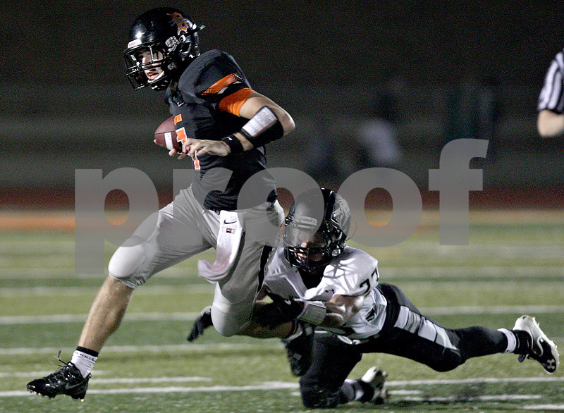 Monica Maschak - mmaschak@shawmedia.com<br /> Quarterback Jack Sauter dodges a tackle attempt only to get sacked moments later in the second quarter against Kaneland at DeKalb High School on Friday, October 4, 2013.