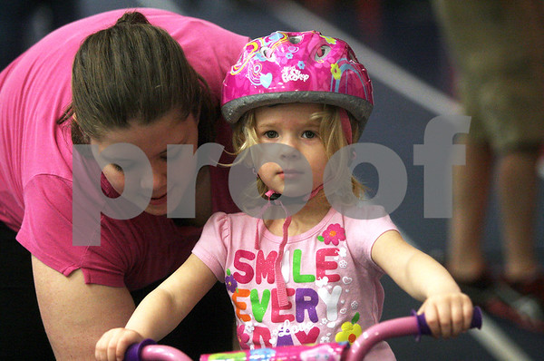 Monica Maschak - mmaschak@shawmedia.com<br /> Paula O'Neil, 3, learns to ride a bike for the first time with the help of her older sister, Rebecca Hungerford, 15, during Healthy Kids Day at the Kishwaukee YMCA on Saturday, April 27, 2013. The event was for kids in the county to get up and get moving as part of a national YMCA movement to promote healthier lifestyles for children. The event featured educational and physical activities such as games for families, bounce houses and a bike rodeo.