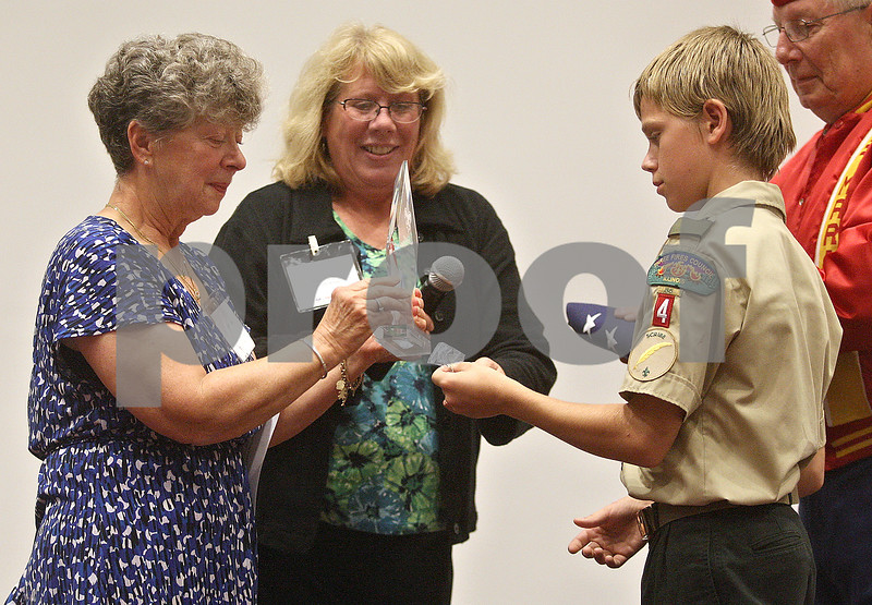 Monica Maschak - mmaschak@shawmedia.com<br /> Denise Curran (left), of Sandwich, accepts an award as one of this year's heroes at the 11th annual DeKalb County Tribute to Heroes at Kishwaukee College on Thursday, October 3, 2013. The event, put on by the Three Fires Council Boy Scouts of America, honored local individuals for heroic actions and/or exceptional, selfless community service.