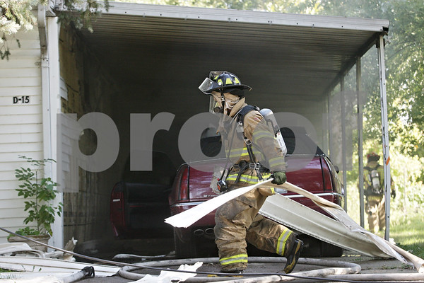 Rob Winner – rwinner@shawmedia.com<br /> <br /> A Sycamore firefighter is seen carrying damaged siding from a mobile home after a fire under the hood of a Cadillac Eldorado was extinguished at Evergreen Village in Sycamore on Monday morning.<br /> <br /> Monday, Sept. 30, 2013