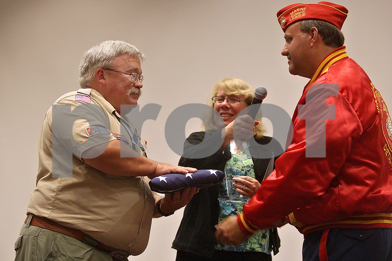 Monica Maschak - mmaschak@shawmedia.com<br /> Dave Lindgren (left), of Shabbona, accepts an American Flag that has seen all four corners of the county at the 11th annual DeKalb County Tribute to Heroes at Kishwaukee College on Thursday, October 3, 2013. The event, put on by the Three Fires Council Boy Scouts of America, honored local individuals for heroic actions and/or exceptional, selfless community service.