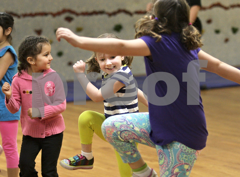 Monica Maschak - mmaschak@shawmedia.com<br /> Molly Fell (center), 5, looks to her sister, Anna Fell, 7, while they learn zumba moves in a Zumbatomic demonstration class during Healthy Kids Day at the Kishwaukee YMCA on Saturday, April 27, 2013. The event was for kids in the county to get up and get moving as part of a national YMCA movement to promote healthier lifestyles for children. The event featured educational and physical activities such as games for families, bounce houses and a bike rodeo.