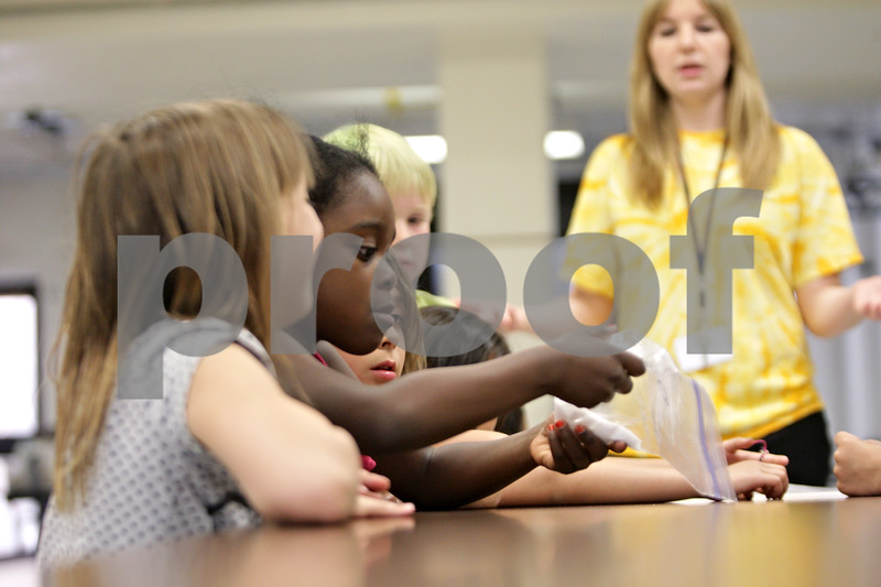 Rob Winner – rwinner@shawmedia.com<br /> <br /> Second-grader Jasmine Young (second from left) looks at a bag of sugar which is the equivalent amount of sugar contained in a glass of apple juice during a Coordinated Approach to Child Health (CATCH) training day at West Elementary School in Sycamore, Ill., Monday, May 20, 2013.