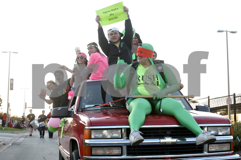 Rob Winner – rwinner@shawmedia.com<br /> <br /> Members of Sigma Alpha Mu ride on a pickup truck during the Northern Illinois University homecoming parade while traveling east on Lucinda Avenue in DeKalb, Ill., Friday, Oct. 11, 2013.