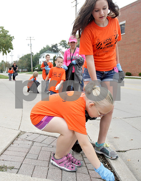 Monica Maschak - mmaschak@shawmedia.com<br /> Alaina Obed (left, blonde), 8, and Sophie McComb, 12, make their way for pieces of trash on Sacramento Street in Sycamore for Kids Word Day on Saturday, October 5, 2013. Local children volunteered to rid Downtown Sycamore of litter to prepare for this year's Pumpkin Festival.