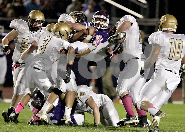 Monica Maschak - mmaschak@shawmedia.com<br /> Syacmore's defensemen uproot Rochelle's quarterback during the first quarter at Rochelle on Friday, October 11, 2013.