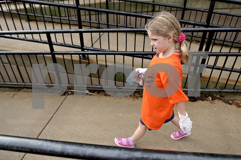 Monica Maschak - mmaschak@shawmedia.com<br /> Samantha Calligan, 7, walks down the Sycamore Post Office ramp after picking up garbage during Kids Word Day on Saturday, October 5, 2013. Local children volunteered to rid Downtown Sycamore of litter to prepare for this year's Pumpkin Festival.