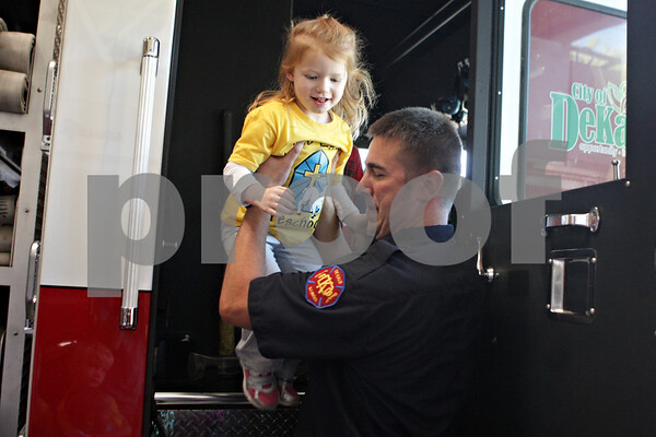 Rob Winner – rwinner@shawmedia.com<br /> <br /> Cassidy Cavazos, 3 of DeKalb is helped down from a fire engine by firefighter Wade Schneck during a tour at Fire Station No. 1 of the DeKalb Fire Department for Fire Prevention Week on Tuesday, Oct. 8, 2013.