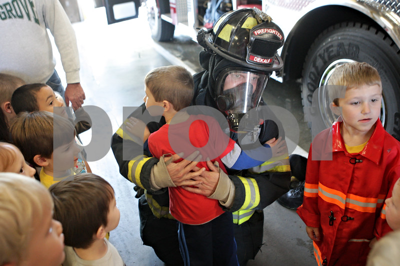 Rob Winner – rwinner@shawmedia.com<br /> <br /> Ben Jones, 4 of Cortland, hugs firefighter Travis Karr during a tour at Fire Station No. 1 of the DeKalb Fire Department for Fire Prevention Week on Tuesday, Oct. 8, 2013.