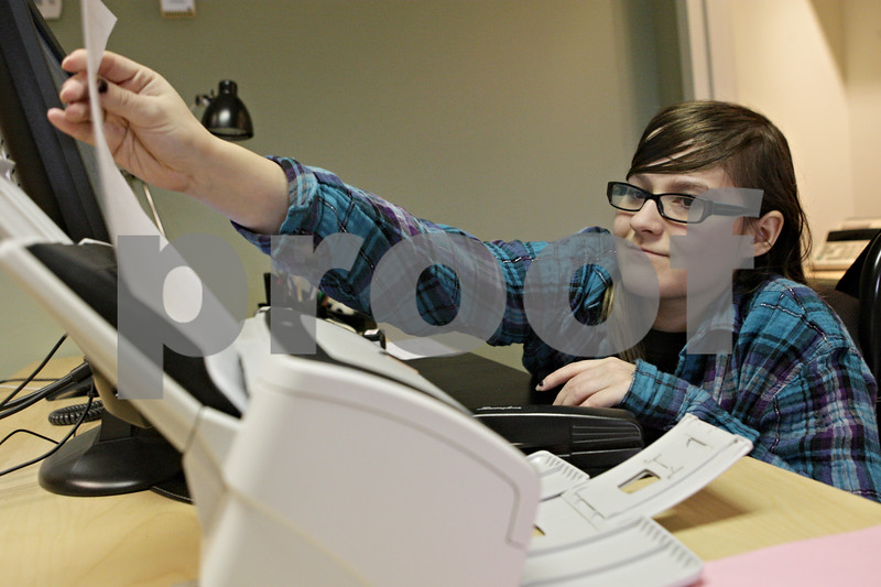 Rob Winner – rwinner@shawmedia.com<br /> <br /> Sycamore High School senior Emily DeCoster, 17, scans documents at the Chief County Assessment Office in Sycamore on Thursday, Oct. 3, 2013. DeCoster began her internship at the office about a month ago.