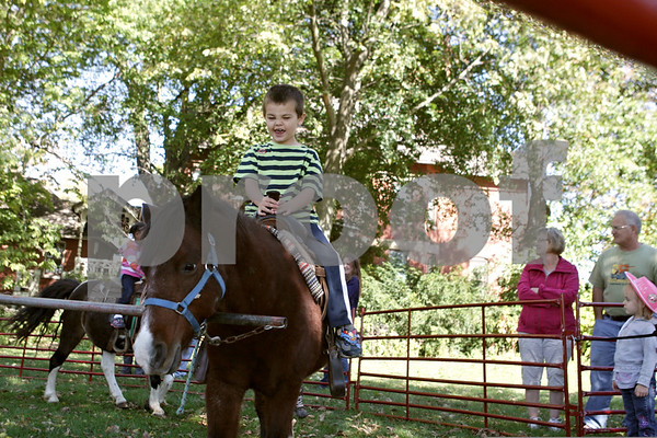 """Rob Winner – rwinner@shawmedia.com<br /> <br /> On Monday afternoon, Jaden Rogers, 5, of DeKalb says """"giddy-up,"""" during a pony ride outside the DeKalb Public Library as part of the Big Read event recognizing the book """"True Grit."""""""