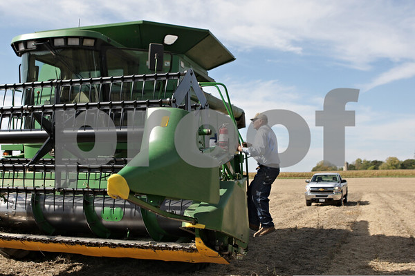Rob Winner – rwinner@shawmedia.com<br /> <br /> Gene Miller climbs back into his combine while harvesting a field of soybeans near Old State and Larson roads in Sycamore, Ill., Thursday, Oct. 10, 2013.