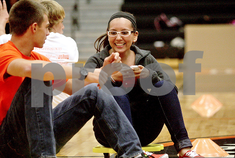 Monica Maschak - mmaschak@shawmedia.com<br /> Junior Cheyenne Nunez scoots herself through an obstacle while texting to demonstrate destracted driving during an assembly at DeKalb High School on Thursday, October 17, 2013. The Barbs could potentially win $100,000 and a free Kelly Clarkson concert depending on the amount of students and community members that pledge to drive safely every day from October 18 through 26.
