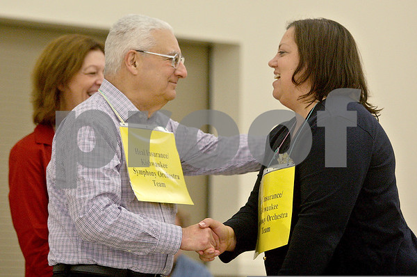 Monica Maschak - mmaschak@shawmedia.com<br /> Jerry Zar congratulates his teammate, Christine Monteiro, for spelling the word irreconcilable in the 10th round to win the 14th Annual DeKalb County Community Spelling Bee at St. Mary's in Sycamore on Thursday, October 17, 2013. The bee raises money for literacy programs DeKalb County.