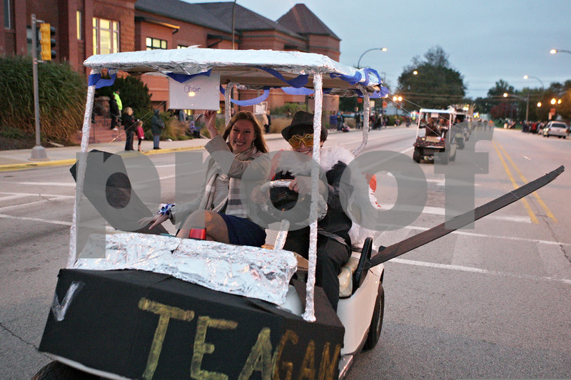 Rob Winner – rwinner@shawmedia.com<br /> <br /> Teagan Overhaug (left) and Ian Lovell travel west on State Street in a decorated golf cart during Sycamore High School's homecoming parade on Wednesday, Oct. 16, 2013.