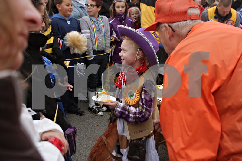 "Rob Winner – rwinner@shawmedia.com<br /> <br /> Savanna Dean, 7, gets one of the first pieces of cake during Wednesday's opening ceremony at the Sycamore Pumpkin Festival. Dean submitted the winning entry in the 2013 Pumpkin Festival contest. Savanna's theme is ""Pumpkin Adventures."""